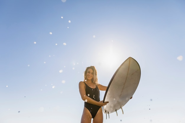 Happy woman standing with surfboard in hands