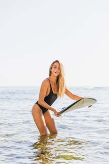 Happy woman standing with surfboard in sea