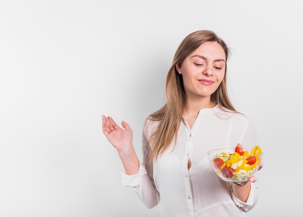 Happy woman standing with vegetable salad in bowl