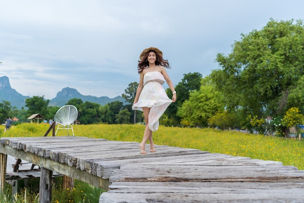 Happy woman standing on wooden bridge with yellow cosmos flower field