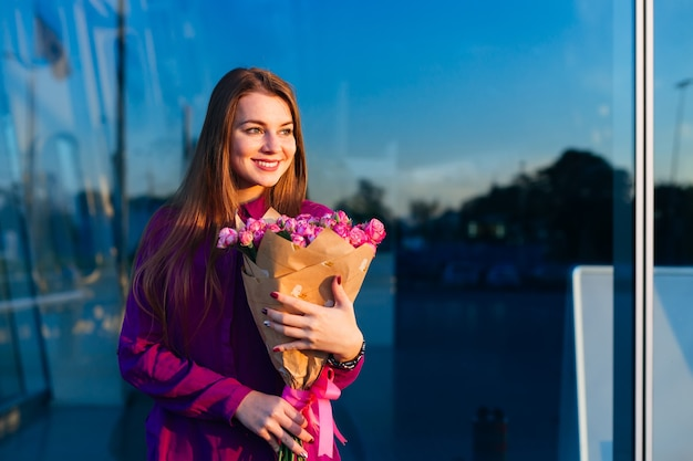 Happy woman stands with pink roses on contarst background