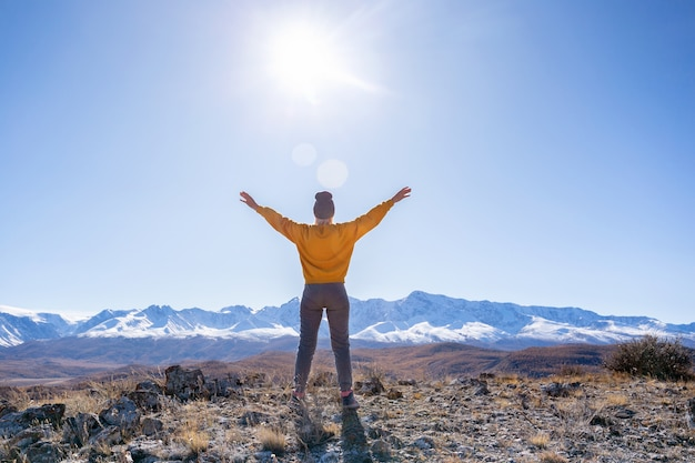 Happy woman stands with raised hands on mountains