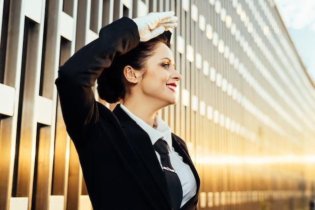 制服を着た幸せな女性スチュワーデスが空を見上げる
