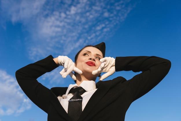 空の背景にカメラでポーズをとって制服の幸せな女性スチュワーデス