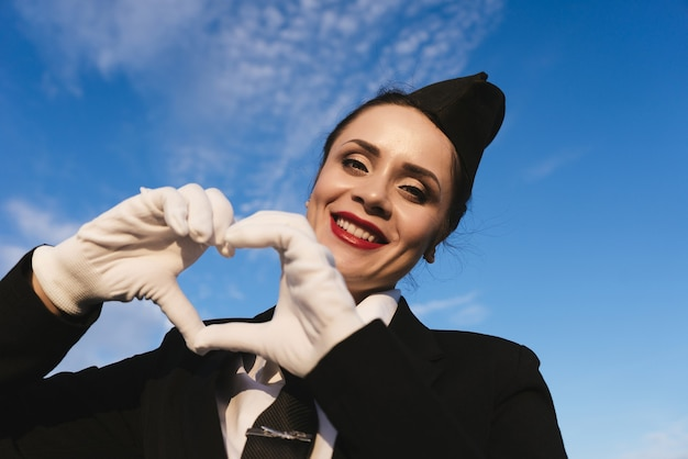 Happy woman stewardess in uniform on a background of blue sky shows heart