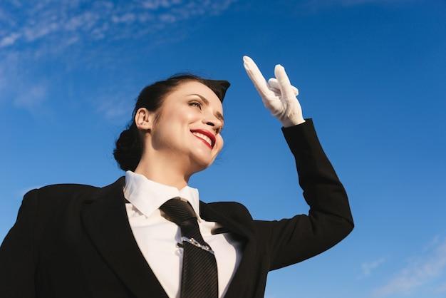 Happy woman stewardess in uniform on blue sky background