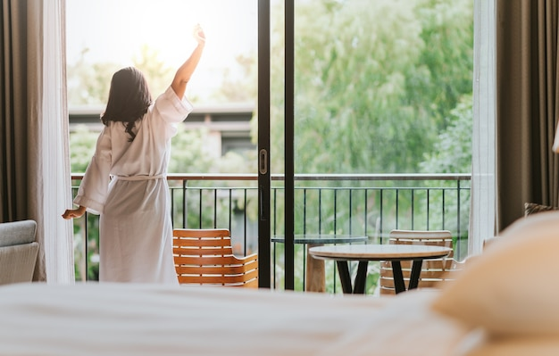 Happy woman stretches and opens the curtains at window in morning.