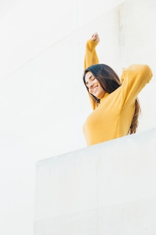 Happy woman stretching at balcony