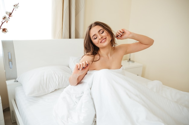 Happy woman stretching hands in the bed at home