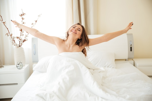 Happy woman stretching hands on the bed at home