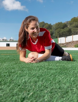 Happy woman stretching leg on field