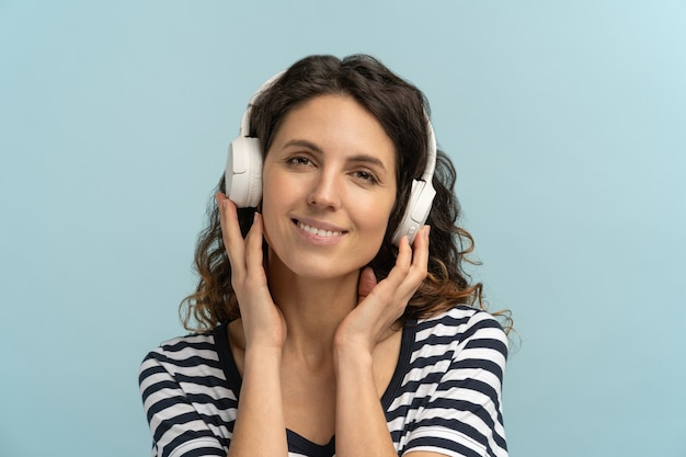 Happy woman in stripped t-shirt wear wireless headphones listening to music, keeps hands on headset