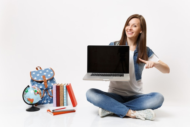 Una studentessa felice che punta il dito sul computer portatile con schermo vuoto nero vuoto si siede vicino al globo, libri di scuola zaino isolati