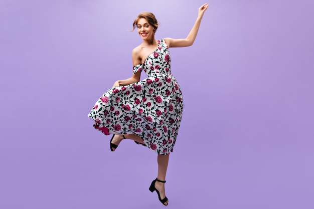 Happy woman in stylish dress jumps on purple background. joyful attractive girl in floral trendy outfit posing on isolated backdrop.