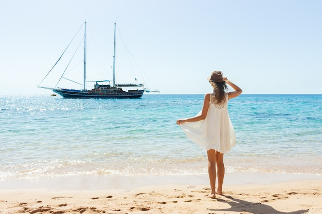 Happy woman in summer dress on beach. girl relaxing and enjoying peace on vacation