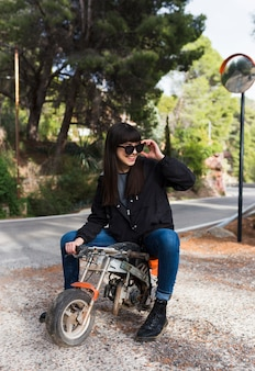 Happy woman in sunglasses sitting on mini motorcycle