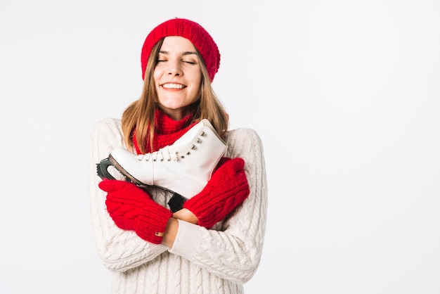 Happy woman in sweater holding skate