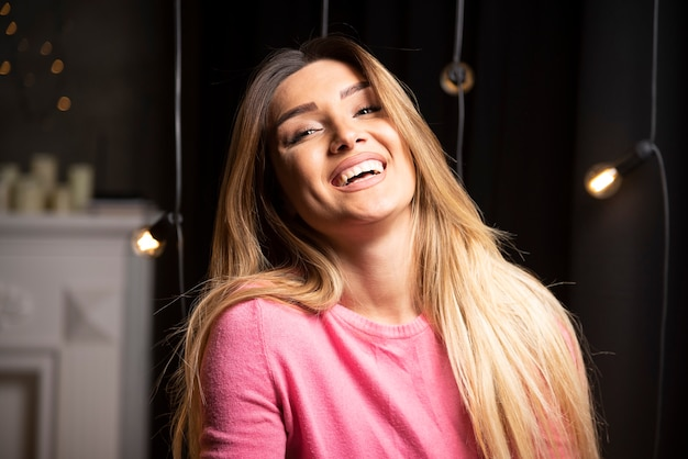 Una donna felice in maglione in posa vicino a lampade leggere. foto di alta qualità
