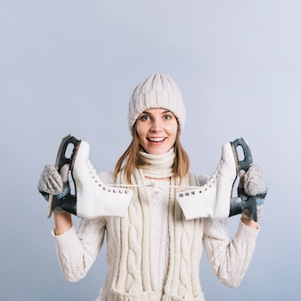 Happy woman in sweater with skates