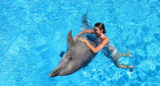Happy woman swims with cute dolphin in blue water.