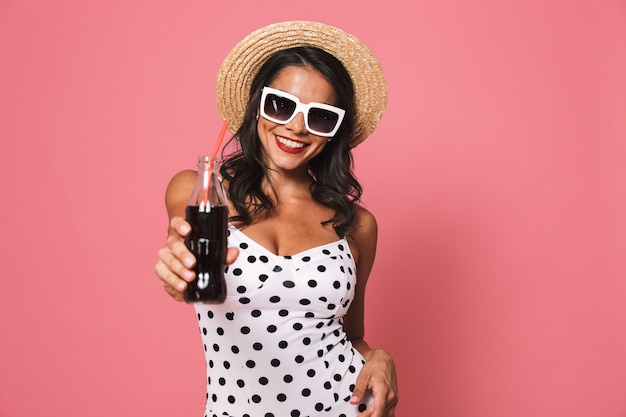Happy woman in swimwear drinking soda
