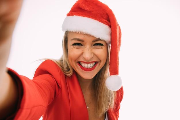幸せな女性は自分と笑顔の写真を撮り、分離された写真
