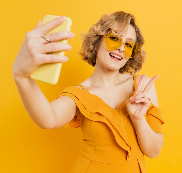 Happy woman taking a selfie while wearing sunglasses