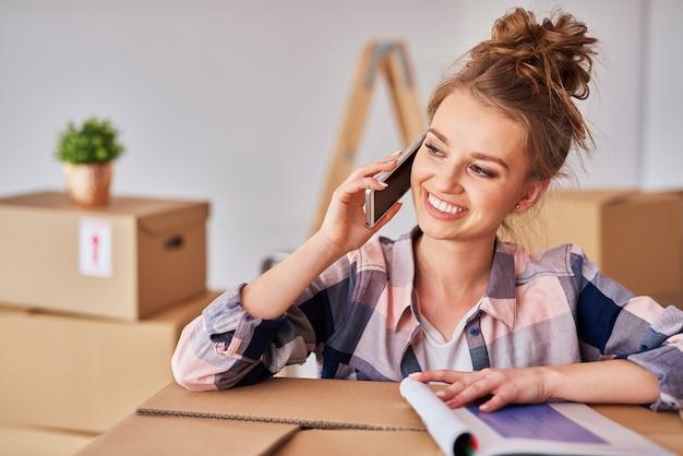 Счастливая женщина разговаривает по мобильному телефону среди коробок