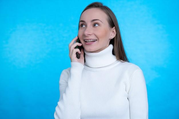 Счастливая женщина разговаривает по смартфону и смотрит в сторону