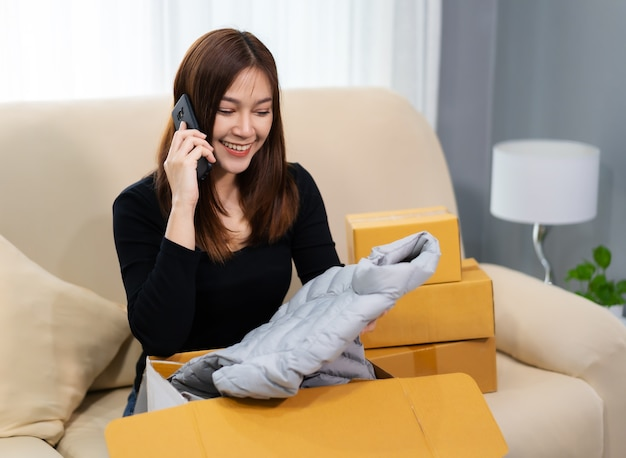 携帯電話で話し、段ボールの小包ボックスを開梱する幸せな女性