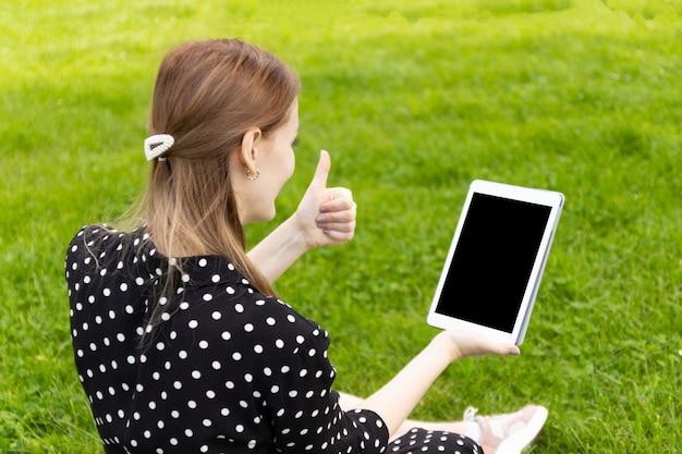 Счастливая женщина разговаривает по линии в видеоконференции с ноутбуком, сидя на скамейке на улице