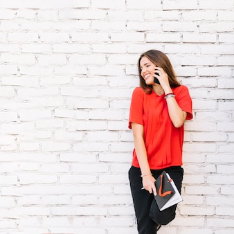Happy woman talking on mobile phone against brickwall