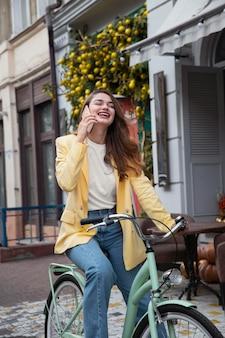 屋外で自転車に乗ってスマートフォンで話している幸せな女性