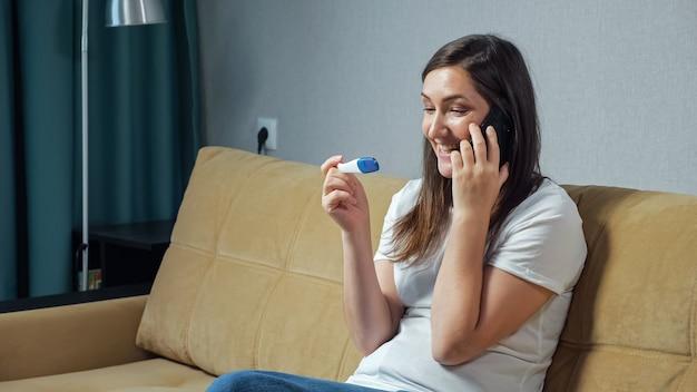 妊娠検査を手に持って電話で話している幸せな女性。