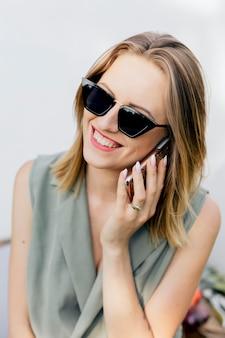 彼女の庭で電話で話している幸せな女性