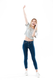 Happy woman talking on phone and raising hand