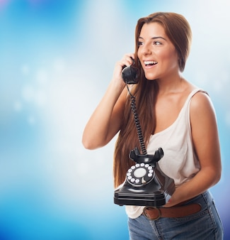 Happy woman talking over phone with handset