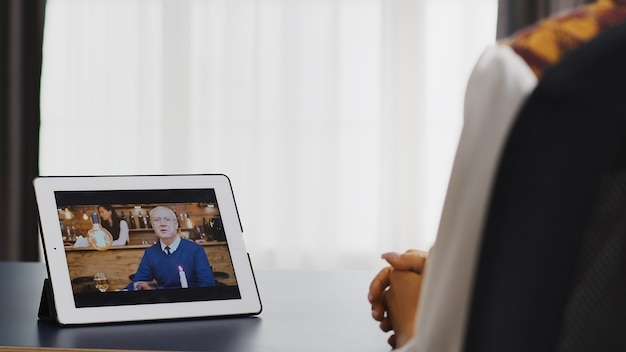 Happy woman talking with her father on a video call using tablet computer.