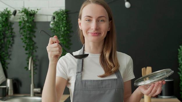 幸せな女性はおたまからスープを味わい、キッチンで微笑む
