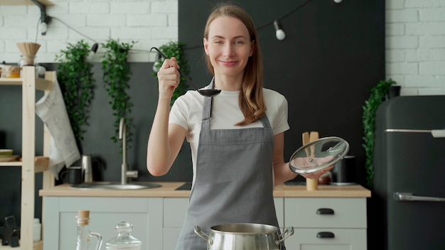 Happy woman tastes soup from a ladle and smiles in the kitchen