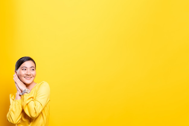 Happy woman thinking and standing isolated over yellow wall
