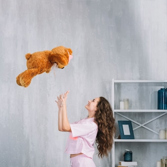 Happy woman throwing soft toy in mid-air at home