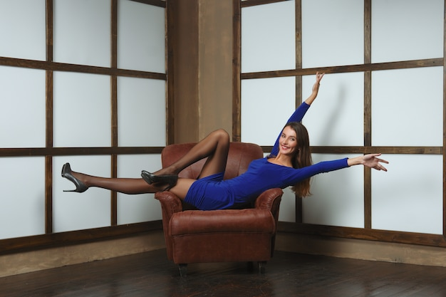 Happy woman in tight short dress half laying in leather armchair with hands up