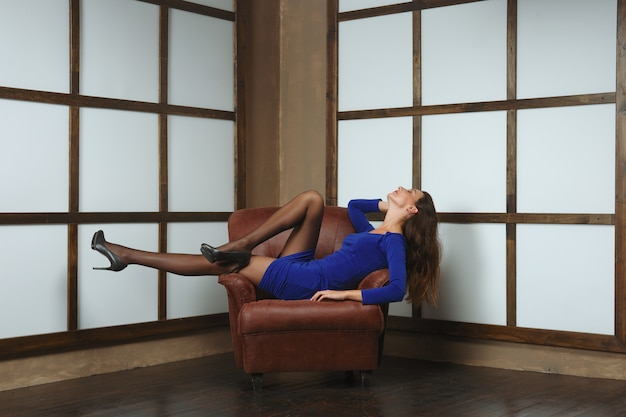Happy woman in tight short dress half laying in leather armchair