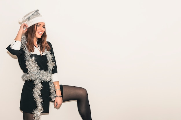 Happy woman in tinsel and santa hat