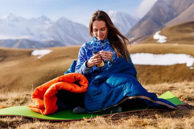 Счастливая женщина-турист пьет чай на фоне красивых гор