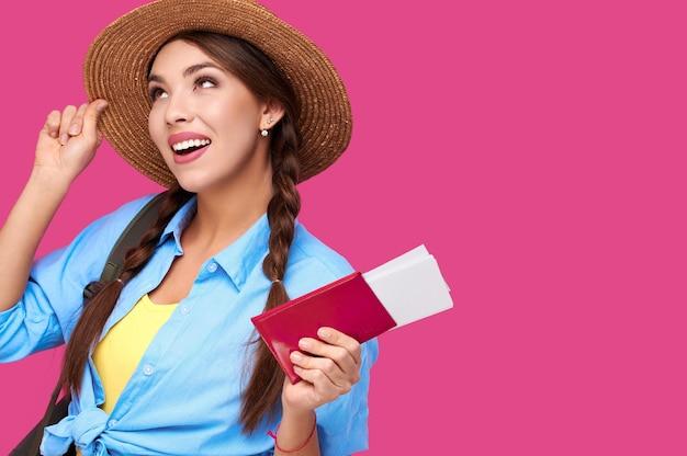 ピンクの孤立した背景で休日にパスポートと飛行機の休暇のチケットを保持している夏のカジュアルな服で幸せな女性の観光客