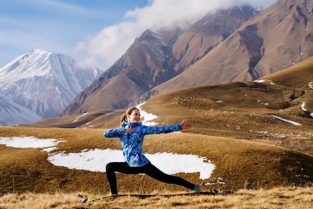 Счастливая женщина-турист на фоне высоких гор делает упражнения