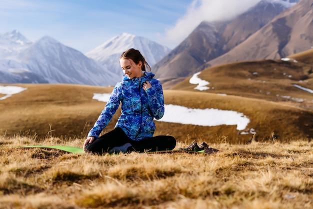 Счастливая женщина-турист на фоне высоких гор в солнечный день, практикующих йогу