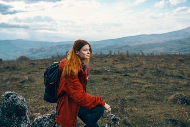 幸せな女性の観光客は、自然の山々の中の牧草地で休むために座った